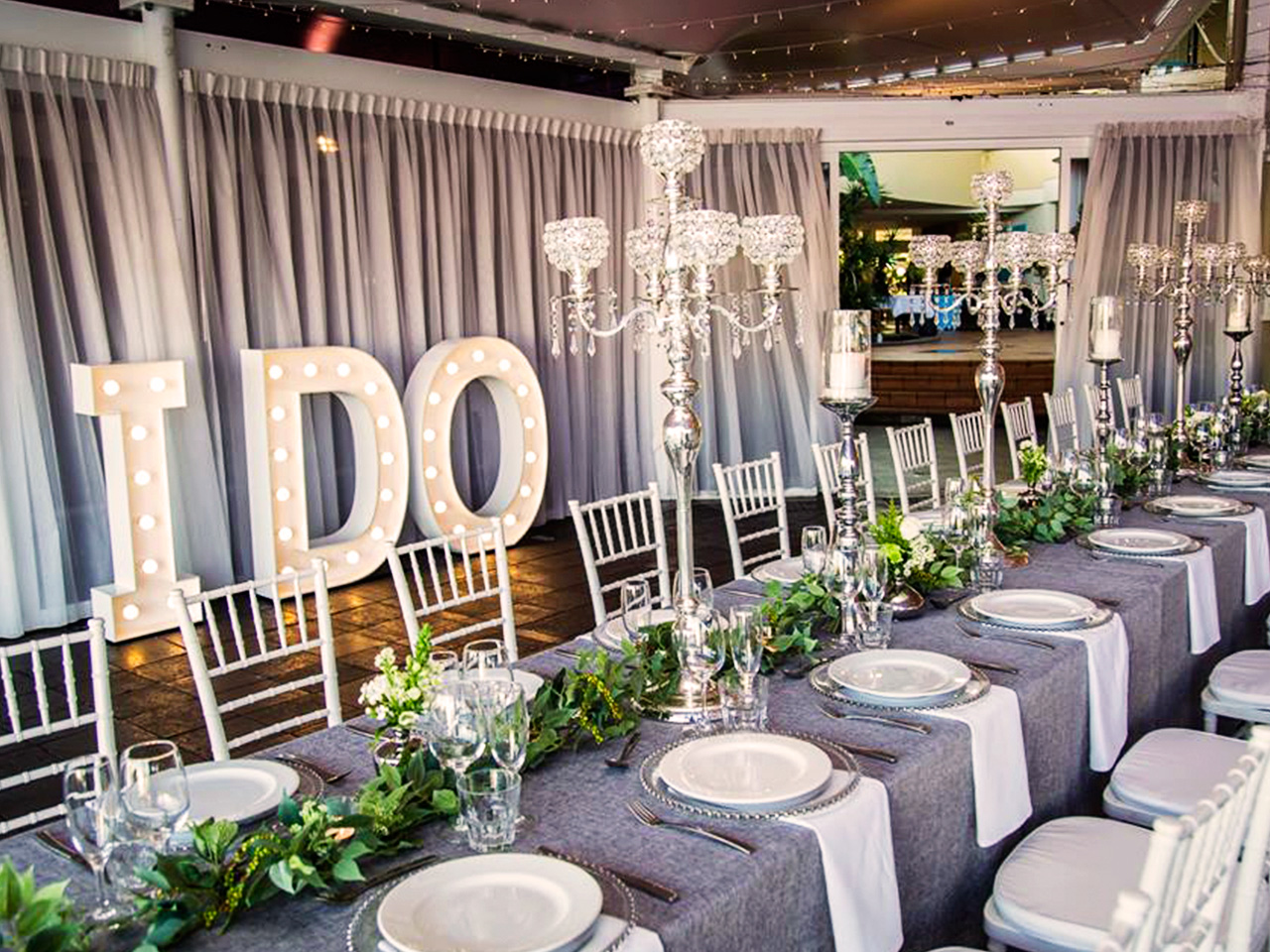 Chairs And A Long Table Setup With Green Leafy Centerpieces And 'I Do' Standee Inside The Function Room