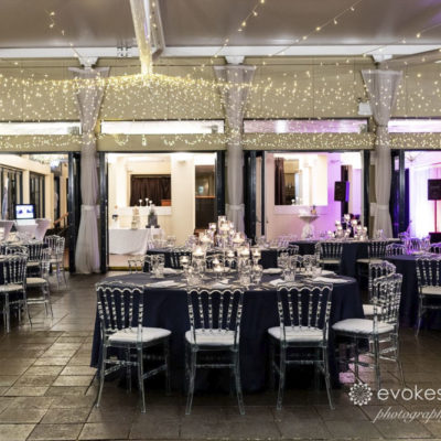Chairs And Tables In Banquet Style With String Lights Inside The Function Room