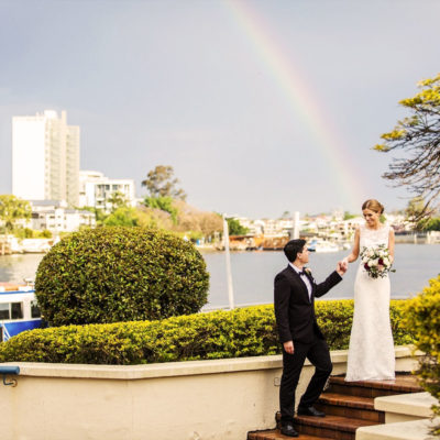 Groom assisting bride down stairs overlooking Brisbane river