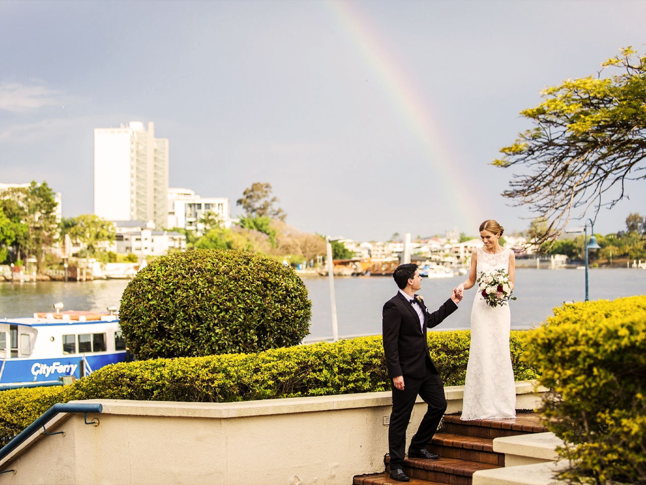 Groom assisting bride down stairs overlooking Brisbane river