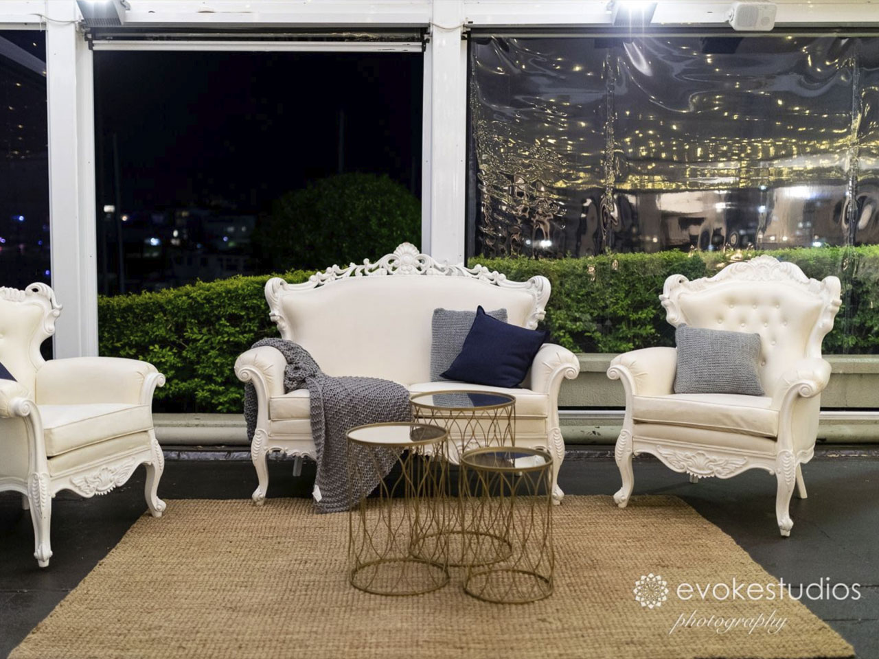 White lounge chairs at window at night time inside function room