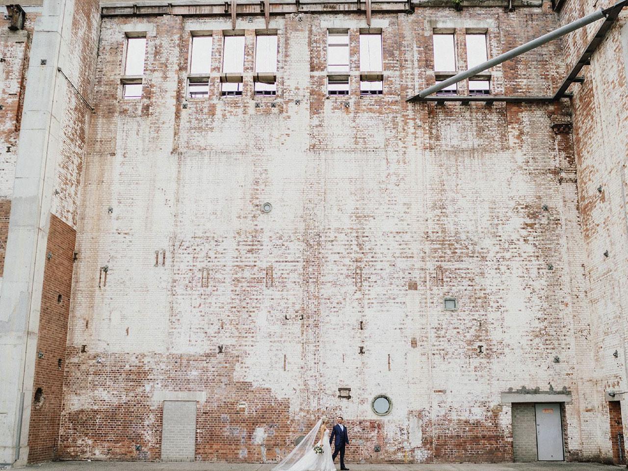 Wedding couple walking past huge white wall
