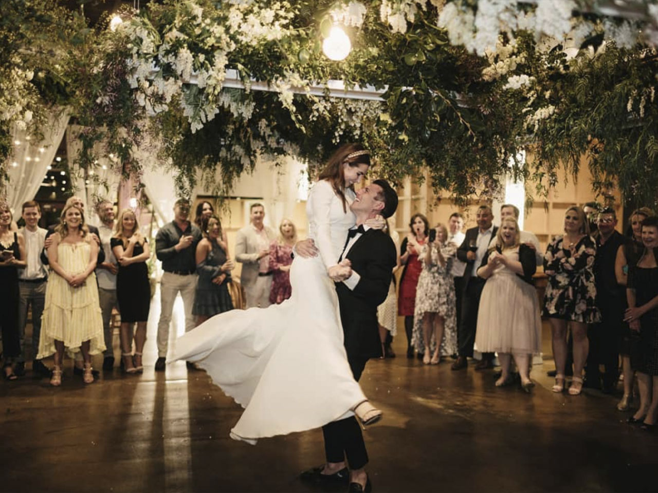 Wedding couple dancing on wooden dance floor in front of crowd