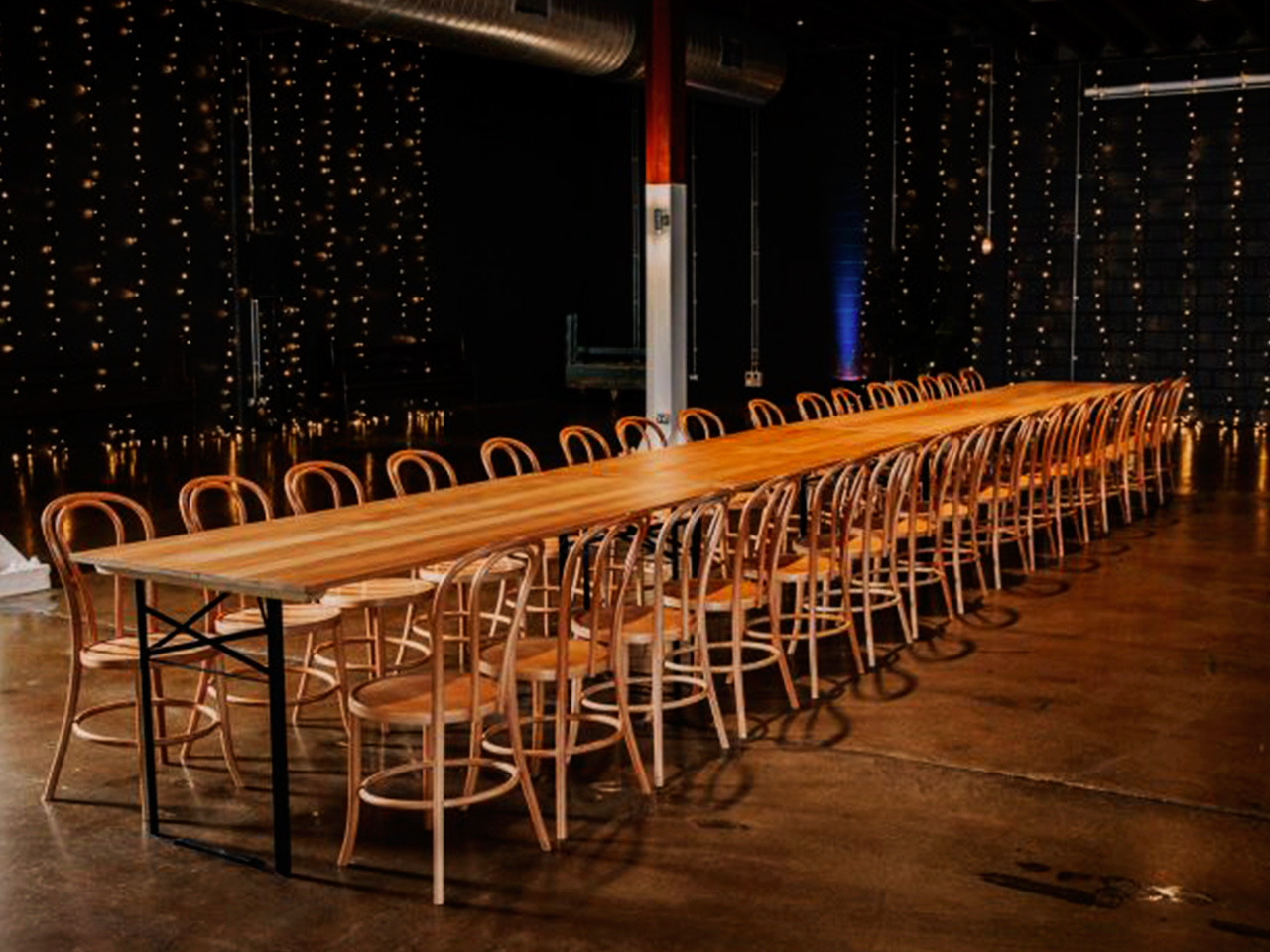 Long Table with Chairs Inside The Function room With String Lights On The Wall