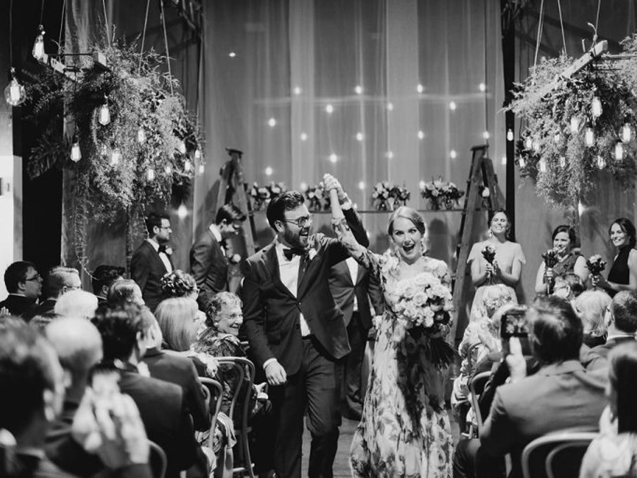 Black and white image of couple walking down the aisle between rows of seated guests