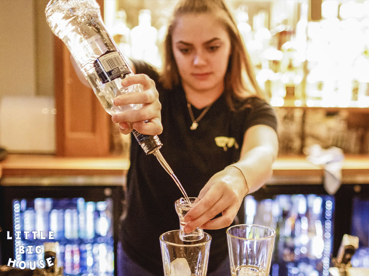 Bar girl pouring spirits into small glass at bar