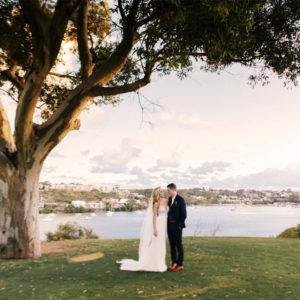 Wedding couple underneath tree overlooking Swan River