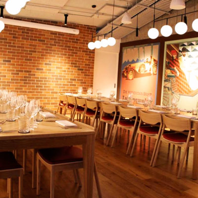 Two Long Tables With Chairs Inside The Function Room With Brick Walls And Warm Lighting