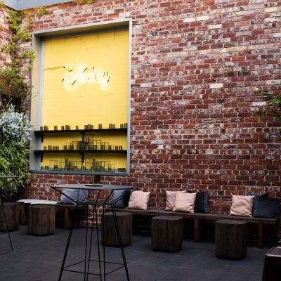 Outside The Event Venue. Open-Air Extension With Brick Walls, Plants, Wooden Chairs And Table