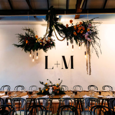 A Long Table With Chairs, Backdrop And Hanging Flower Design