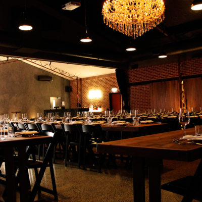 Long Tables And Chairs Setup for An Event With Warm Lighting And Chandelier