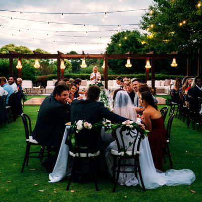 Guests With The Groom And Bride Seated In Long Tables Outside The Function Room With String Lights