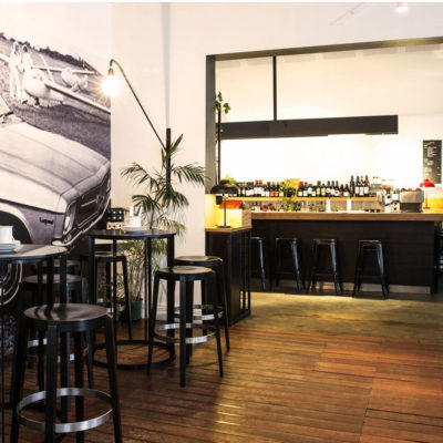 Dining room with mural of car on left and bar seats in background and high chairs and tables