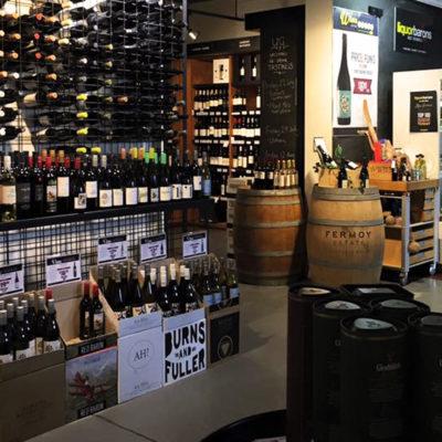 Cellar door with racks of wine and barrels of beer