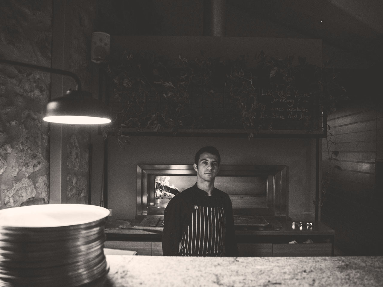 Black and white image of male chef standing in front of pizza over