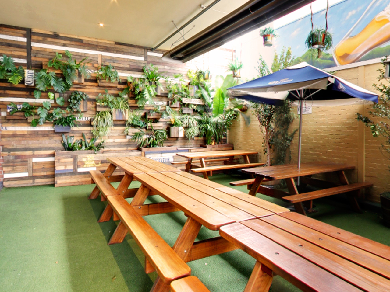 Wooden Tables And Chairs With Umbrellas And Wall With Hanging Plants In The Outdoor Function Venue
