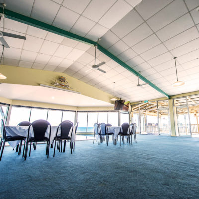 Few Chairs And Tables Inside The Function Room With TV Screen