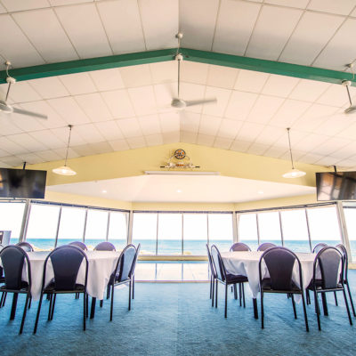 Few Chairs And Tables Inside The Function Room With TV Screens