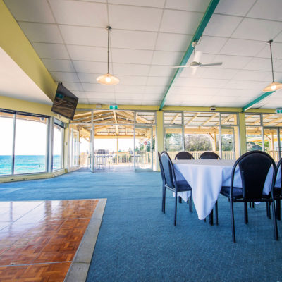 Few Chairs And A Table Inside The Function Room With TV Screen