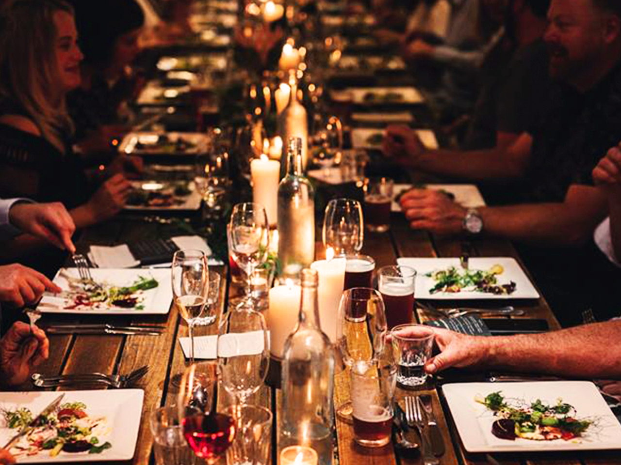 Guests Enjoying Their Food With Drinks on The Table And Candle Lights