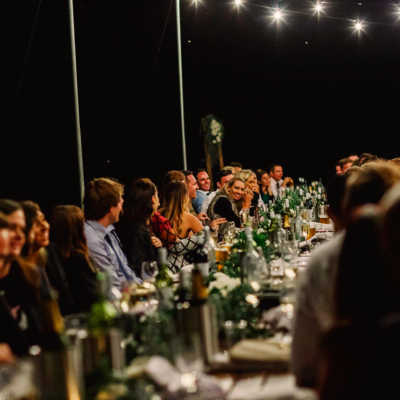 Guests Enjoying The Evening Seated In A Long Table