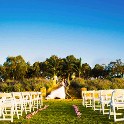 Bride And Groom Taking Photo With White Chairs In Front Of Them