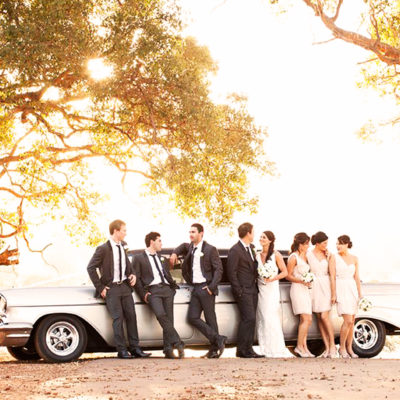 Bride And Groom With The Entourage Taking Photo Under The Trees With A Vintage Car Behind Them