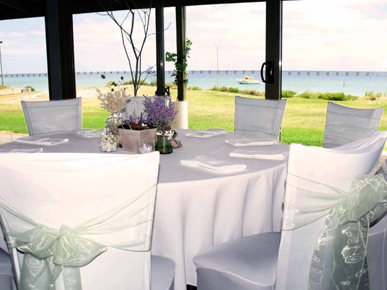 Chairs And Table Setup In Banquet Style Inside The Function Room With Glass Walls And Ocean View