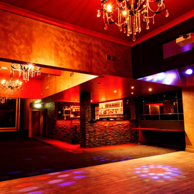 Empty Function Room With Chandelier In Red Lighting And A Dance Floor
