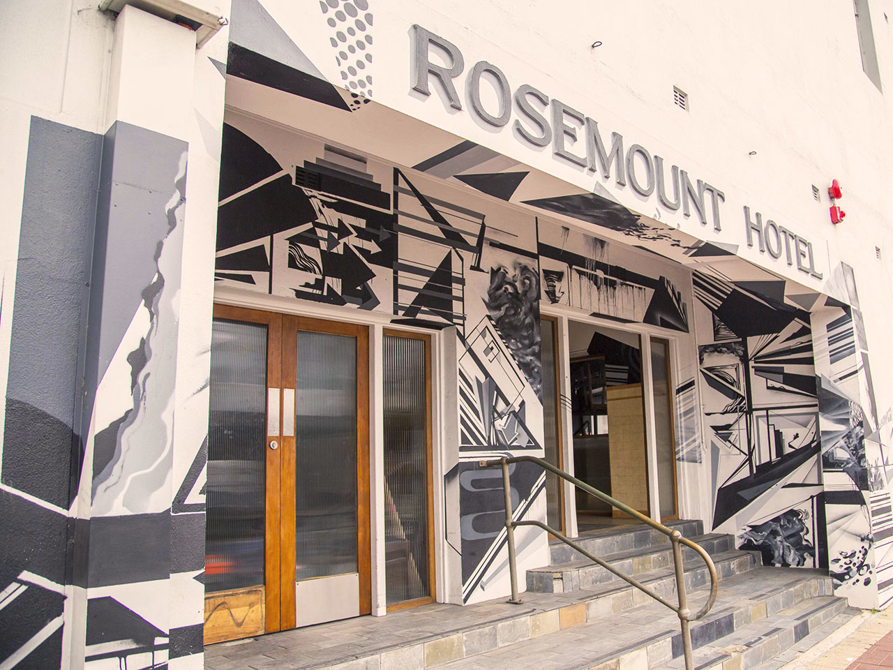 Front entrance to The Rosemount Hotel with steps leading up to wooden doors beneath signage