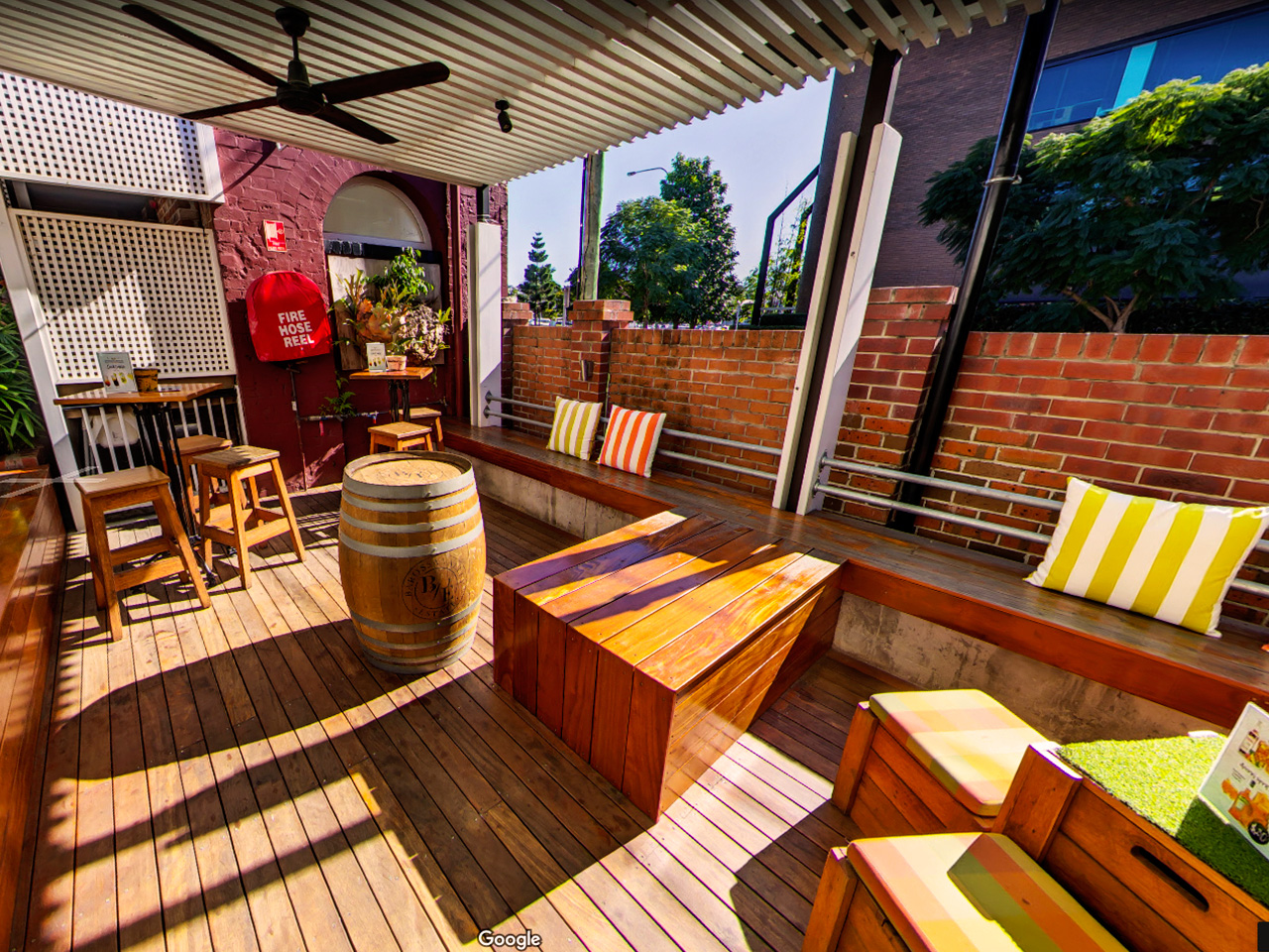 Wooden Chairs And Tables With Wine Cask, A Long Chair On The Side And Stripe Pillows In The Garden Function Space