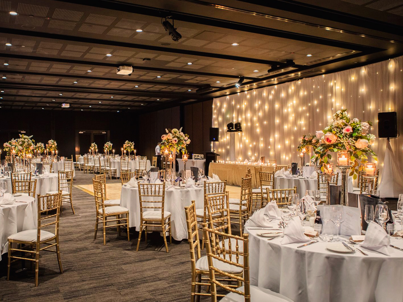 Tables And Chairs In Banquet Style With Flower Centerpieces And String Lights On The Front