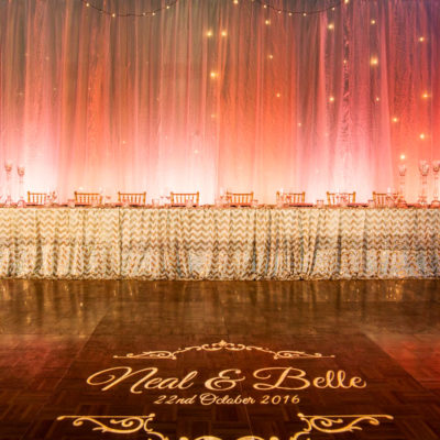 A Long Table With Chairs, Pink Colored Backdrop With String Lights And A Dance Stage In Front