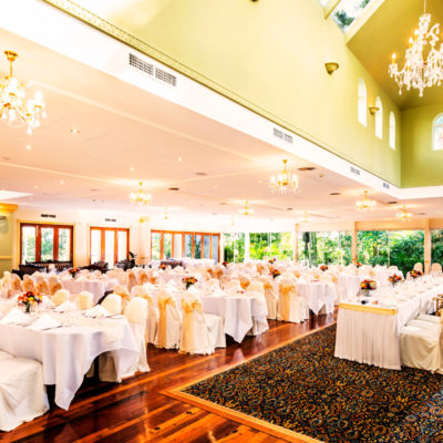 Long Tables And Chairs Setup Inside The Function Room With Chandeliers