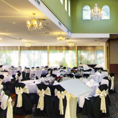 Chairs and Tables In Banquet Style Inside The Function Room With Curtained Windows Backdrop