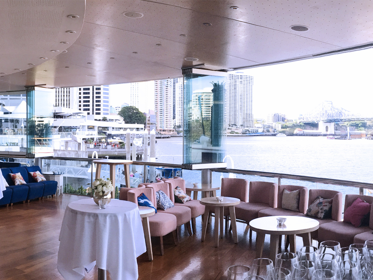 Riverside venue set up for cocktail with round tables and sofa chairs overlooking river