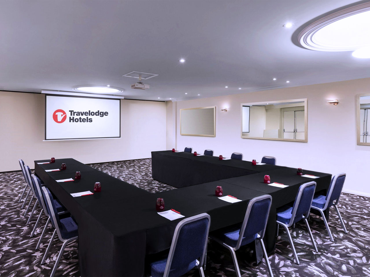Meeting room with u-shaped table arrangement and projector screen