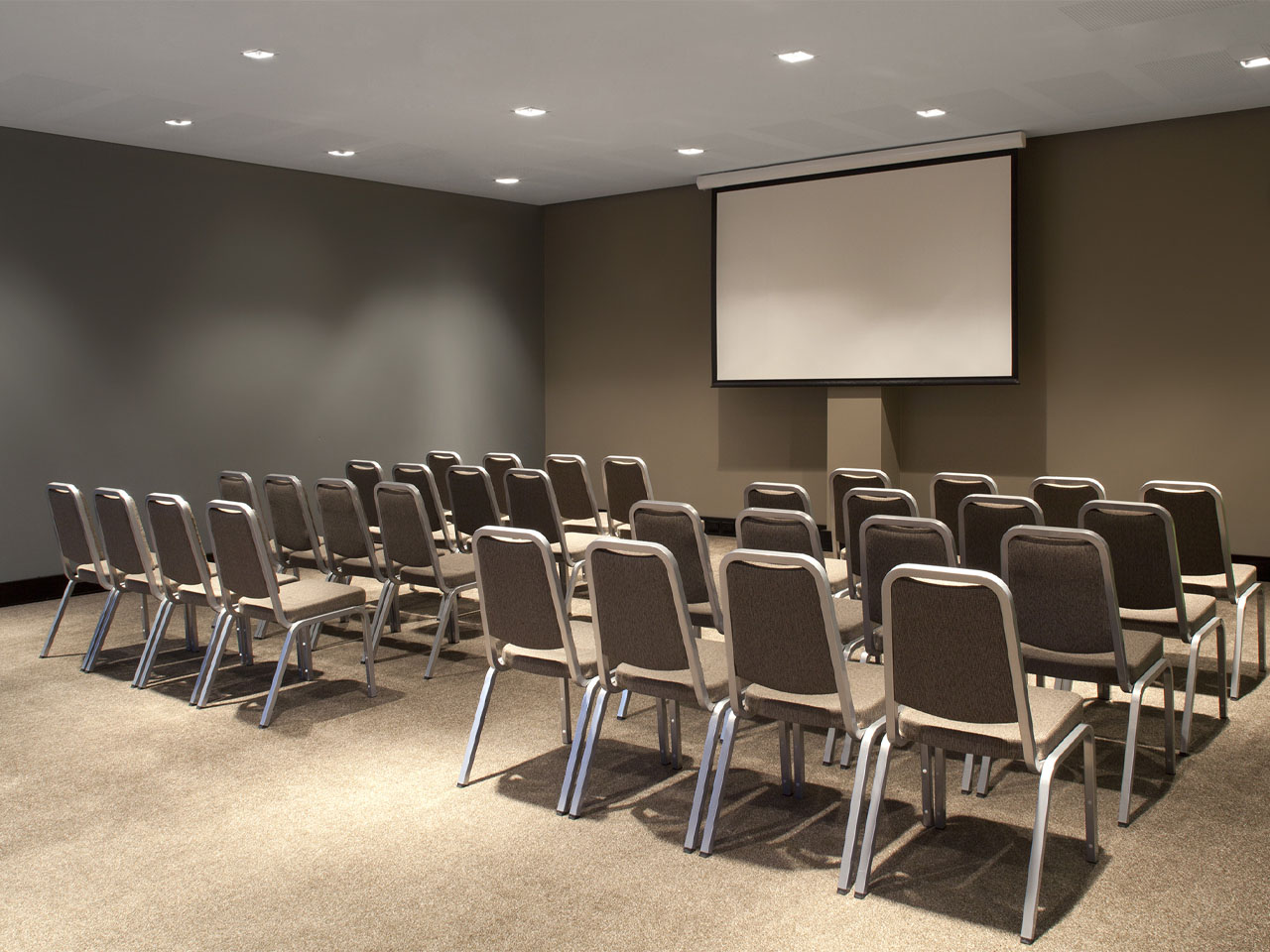 Empty conference room set up with chairs and projector screen