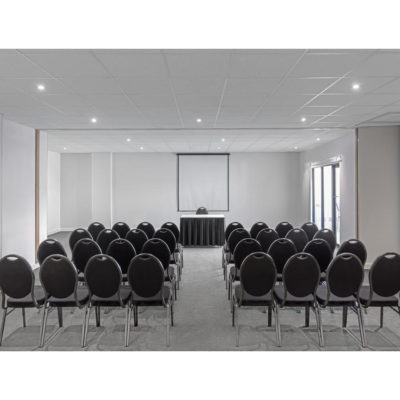 Conference room set up with rows of seats and projector screen