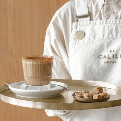 Full cup of coffee with sugar cube bowl on a tray carried by waiter