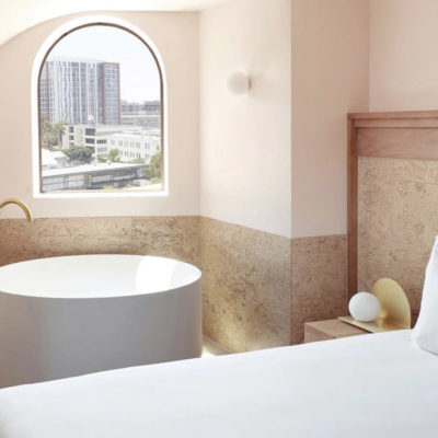 Hotel bedroom with round bath and arched window overlooking Brisbane