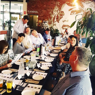 Lunch guests enjoying food at long table in front of brick wall with mural