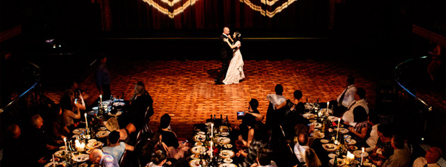 Bride and groom dancing on stage with onlooking seated guests