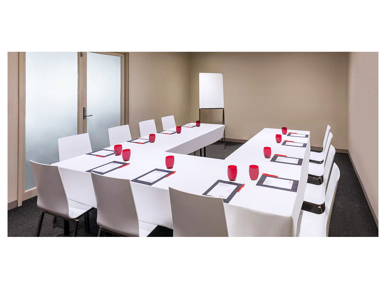 Small meeting room set with white tables and glass door
