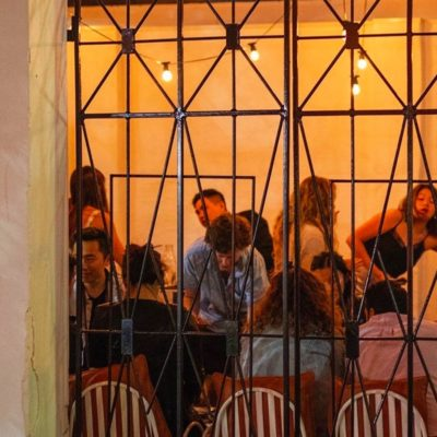 Crowded bar area behind artistic iron decoration