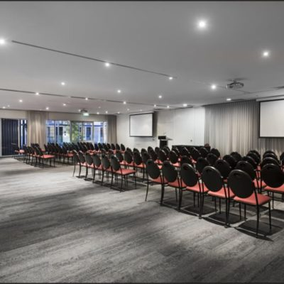 Conference room with rows of black and red seats and projector screen