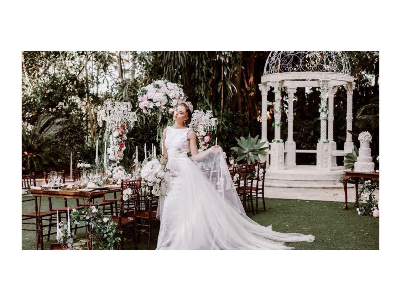 Bride enjoying wedding setting with white gazebo in background