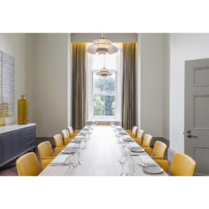 Exclusive dining room with long table and yellow chairs set for lunch