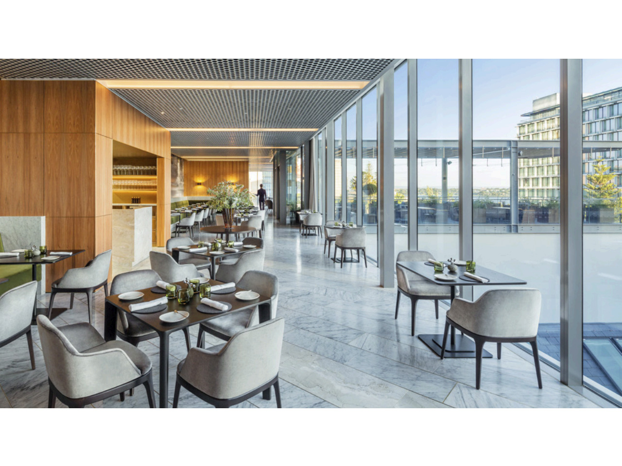 Tables set along glass windows with city outlook