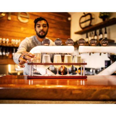 Bartender serving shots of cider in glass rack